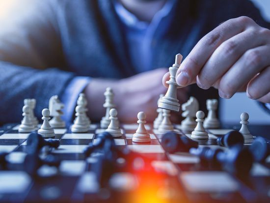 Die Strategie ist entscheidend: Ein Spieler beugt sich übers Schachbrett