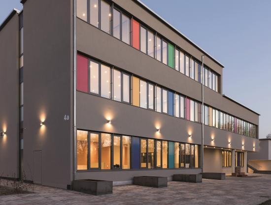 Unter einem Dach: 2017 haben die heute 62 Mitarbeiter und Mitarbeiterinnen den Neubau im Offenburger Ortsteil Rammersweiler bezogen. Das Verlagsgebäude erinnert mit seinen bunten Fensterelementen an eine Grundschule. (Foto: Mildenberger Verlag)