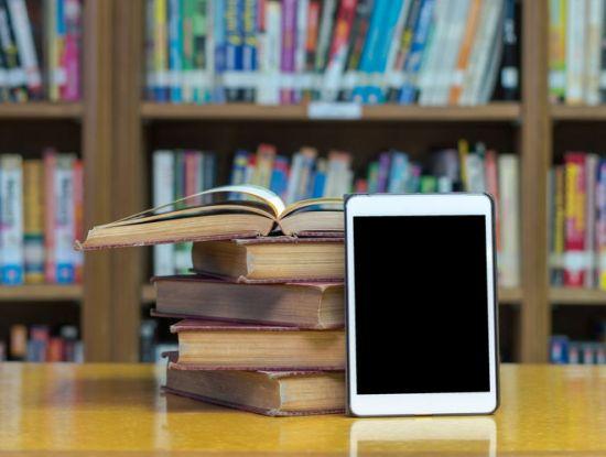 Tablet und Bücher in einer Bibliothek