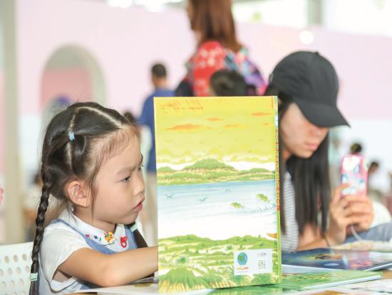 Gucken, lesen, lernen: In China, dem größten Kinderbuchmarkt der Welt, ist es völlig normal, Kinder zu großen buchrelevanten Veranstaltungen mitzunehmen. Während der Pekinger Buchmesse gibt es nicht nur auf dem Messegelände reichlich Gelegenheit, in neuen Büchern zu blättern (Foto). Auch in der Stadt werden Eltern und Nachwuchs an vielen Eventstandorten hofiert. (Foto: Beijing Book Fair)